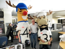 Don poses for a photo with two Famous Racing Sausages in the Journal Sentinel newsroom. Photo courtesy of Sue Walker.